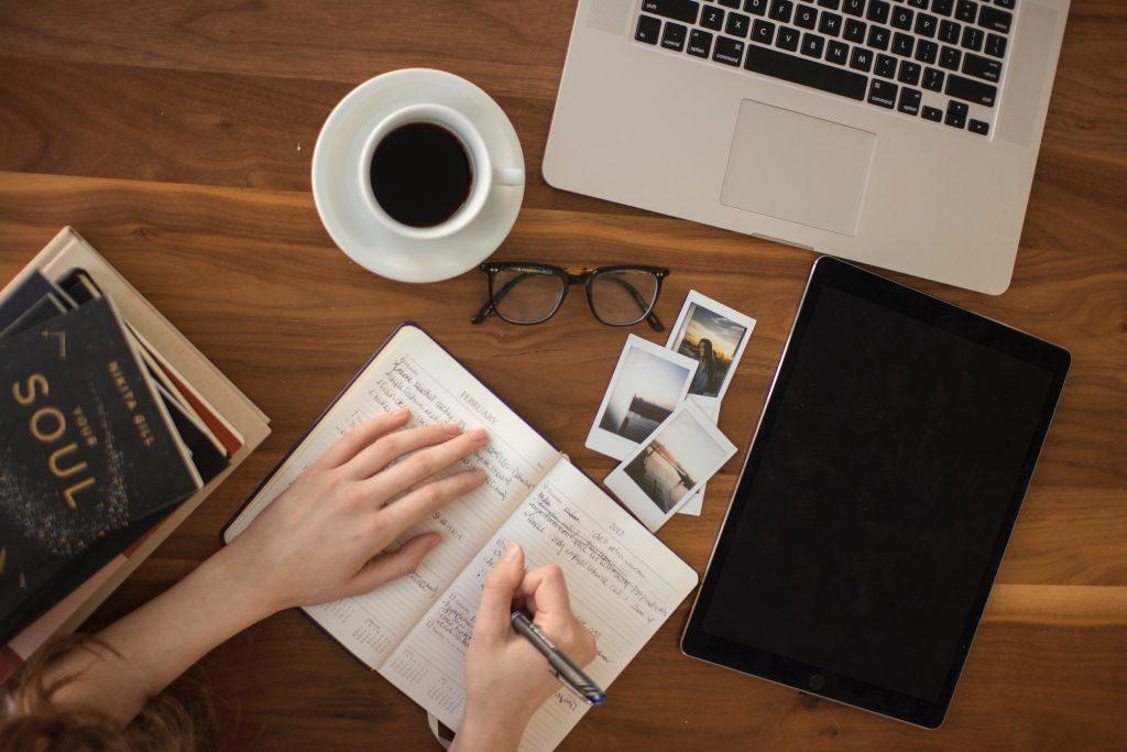 Skrivbord med kaffekopp, anteckningsblock och dator