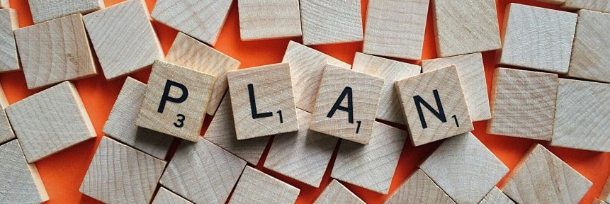 Träbrickor på orange bord, fyra brickor bildar ordet Plan.